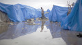 20100226cnsnw01142 1 120x67 - MAN WALKS AT WATERLOGGED TENT CAMP IN PORT-AU-PRINCE