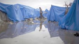 20100226cnsnw01142 1 260x146 - MAN WALKS AT WATERLOGGED TENT CAMP IN PORT-AU-PRINCE