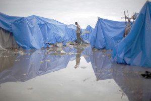 20100226cnsnw01142 1 300x200 300x200 - MAN WALKS AT WATERLOGGED TENT CAMP IN PORT-AU-PRINCE