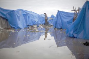 20100226cnsnw01142 1 300x200 - MAN WALKS AT WATERLOGGED TENT CAMP IN PORT-AU-PRINCE