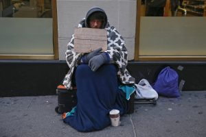 20150116cnsbr7851 1 300x200 - Man holding sign stating he is 'homeless, hungry and cold' sits along sidewalk in New York