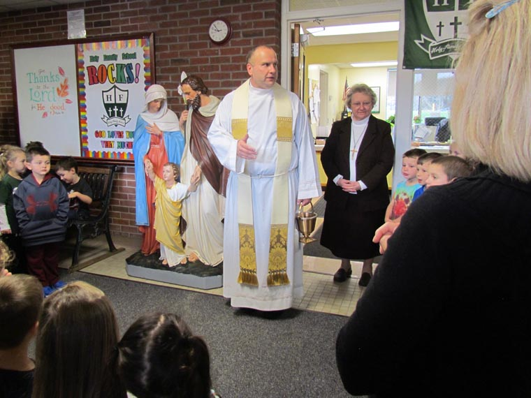 Father Manno blesses restored statue of Holy Family