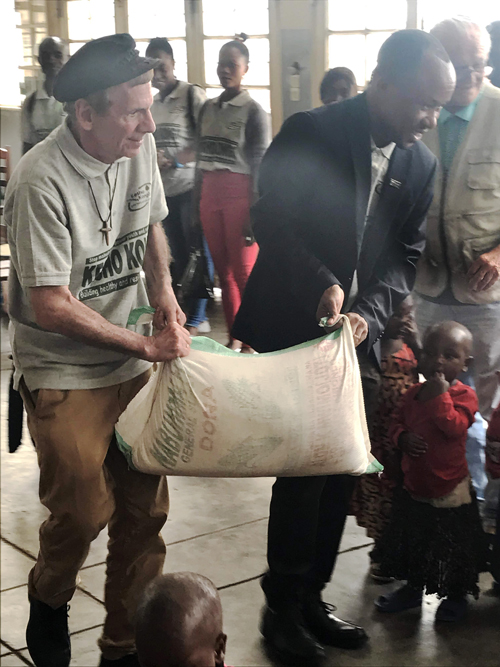 Peter Daino helping Dr. Nyakasane director of Kesho Kongo deliver rice to a nutrition center adjusted - Fierce as a mother